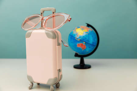 Plastic travel luggage, pink glasses and globe on a table. Traveling concept