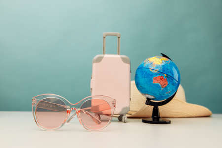 Tourism idea. Plastic travel suitcase, pink glasses and globe on a table