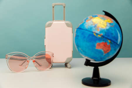 Plastic travel suitcase, pink glasses and globe close-up. Travel concept