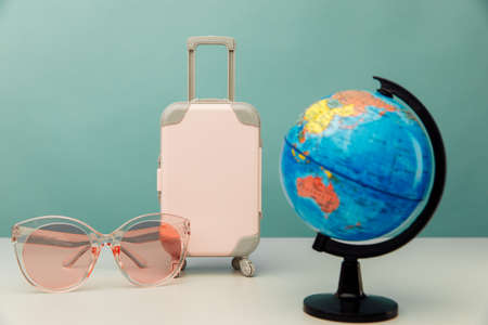Plastic travel luggage, pink glasses and globe on a table. Travel concept