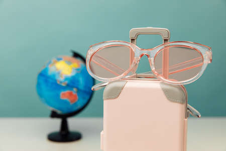 Travel theme. Plastic travel suitcase, pink glasses and globe on a table close-up