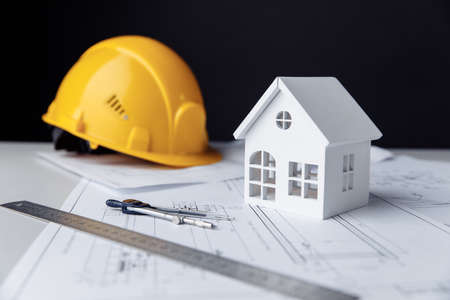 Construction plans with helmet, house and drawing tools on a table 版權商用圖片