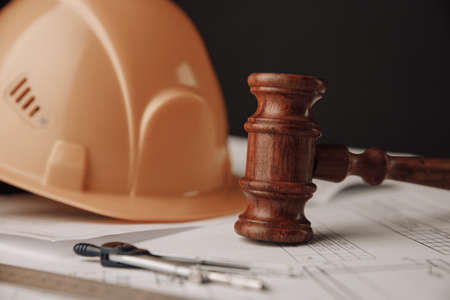 Gavel and construction plans with yellow helmet close-up 版權商用圖片