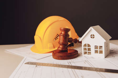 Gavel and construction plans with yellow helmet and house