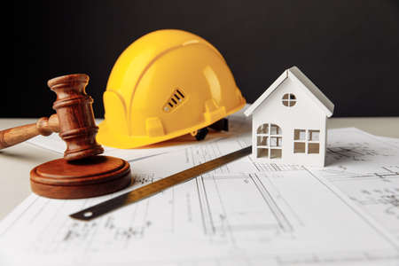 Judge gavel, white house and yellow hard hat with drawing tools 版權商用圖片