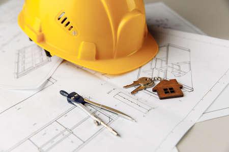 Hard hat, house keys and drawing tools on construction plans 版權商用圖片