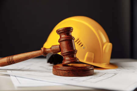 Wooden gavel and yellow helmet on a table with construction plan