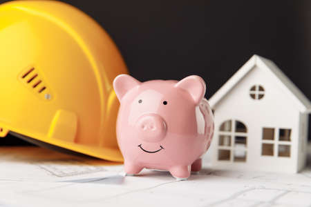 Building costs concept. Yellow safety helmet and pink piggy bank with drawings and model of house close-up 版權商用圖片