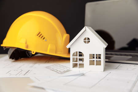 Yellow helmet, house and laptop on construction plans