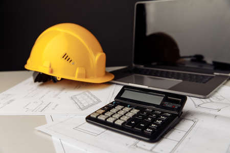 Yellow helmet, calculator and laptop on construction plans