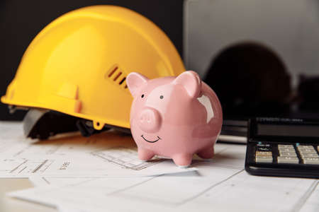 House building costs concept. Safety helmet and piggy bank with blueprint, calculator and laptop