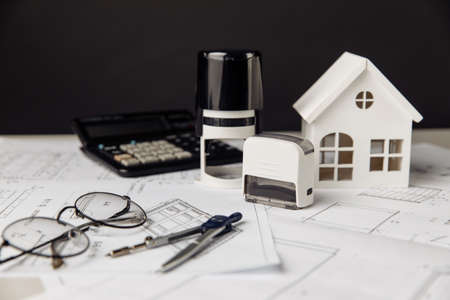 Project blueprint with model of house, calculator and stamps, building costs