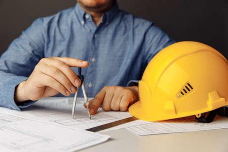 Engineers workplace with helmet and drawing tools. Man working on blueprint 版權商用圖片