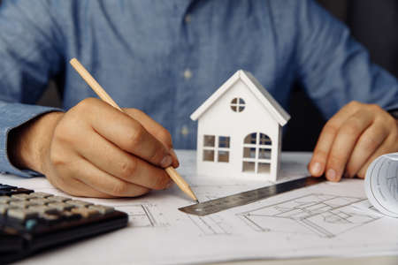 Construction engineer working on blueprint architectural project using pencil