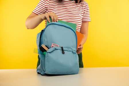Young girl packing backpack with different colorful stationery