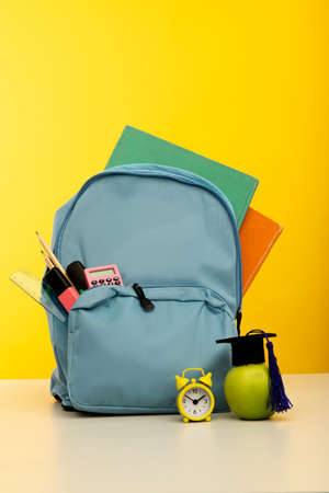 Back to school concept. Backpack with school supplies with alarm clock