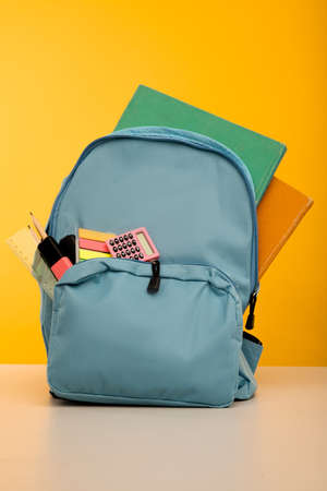 Bright backpack and school stationery on table, vertical image 版權商用圖片
