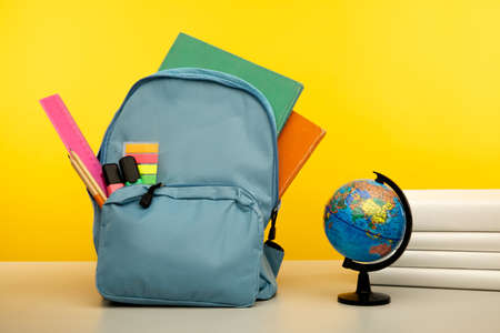 School supplies and globe on a table isolated on yellow. Back to school concept 版權商用圖片
