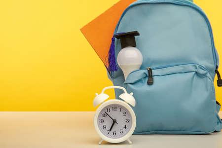 Bright backpack, alarm clock and bulb on a table 版權商用圖片