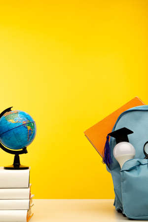 Blue school backpack, globe and bulb on a table. Vertical image