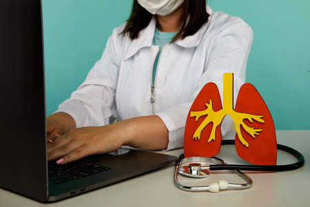 Female doctor is working on laptop, a lung model with a stethoscope on a table. The concept is the importance of early diagnostics