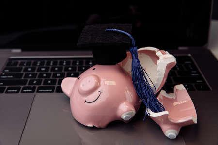 Broken pink piggy bank in cap on keyboard. College, graduate, diploma concept