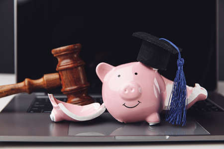 Graduation cap on broken piggy bank on a laptop with wooden gavel. Saving money for education concept