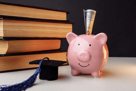 Pink moneybox with stack of books and cap. College, graduate, education, savings concept 版權商用圖片