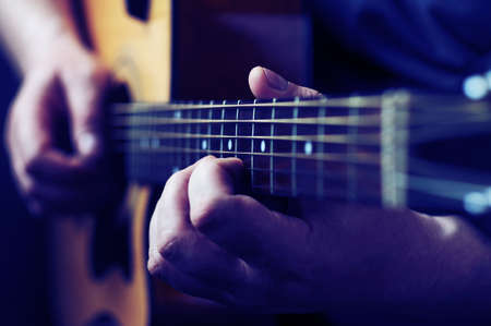 playing instrument: Hands playing acoustic guitar, close up