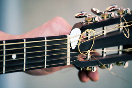 tuning: Hand tuning a guitar from headstock Stock Photo