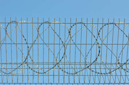 confine: A prickly wire is on a background blue sky. Stock Photo