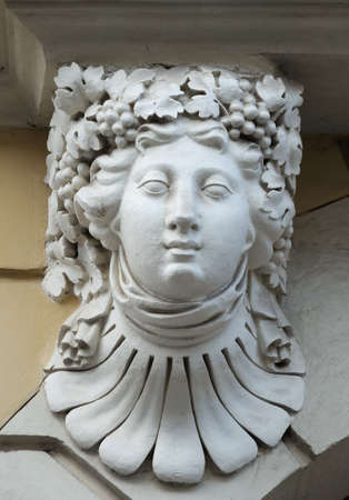 heads old building facade: Statue on the wall in Lviv.