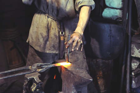 forge: Blacksmith working on metal on anvil at forge high speed detail shot