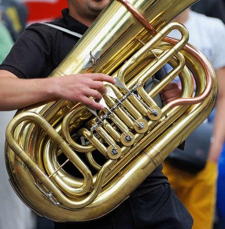 tuba: Musician is playing on the golden tuba.