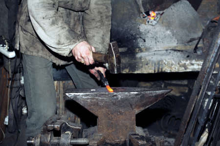 Blacksmith working metal with hammer on the anvil in the forge 写真素材