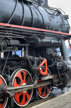 peron: LVIV, UKRAINE - DECEMBER, 2015: Old Soviet vintage black retro train L-3535 at the railway station in Lviv produces steam from the pipes