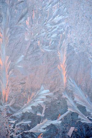 Ice patterns and evening sunlight on winter glass Stock Photo