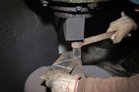 working hands: Blacksmith hammering hot iron automatic hammer