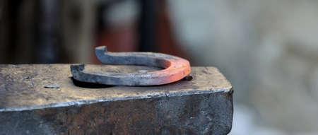 Fabbro forgia un ferro di cavallo per cavallo