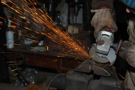 working hands: Heavy industry worker cutting steel with angle grinder