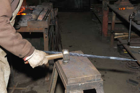 incus: Blacksmith working metal with hammer on the anvil in the forge Stock Photo