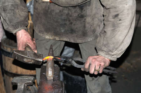 forge: Blacksmith working metal with hammer on the anvil in the forge Stock Photo