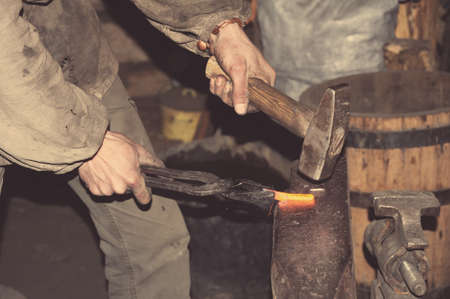 blacksmith shop: Blacksmith working metal with hammer on the anvil in the forge Stock Photo