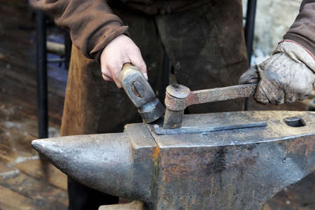 smithy: Blacksmith forges a horseshoe in a smithy