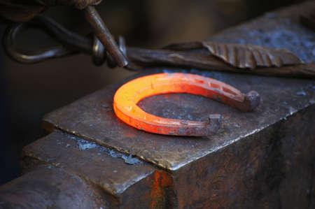 Fabbro forgia un ferro di cavallo in una fucina