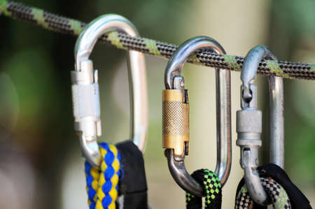 caving: Climbing sports image of a carabiner on a rope in a forest