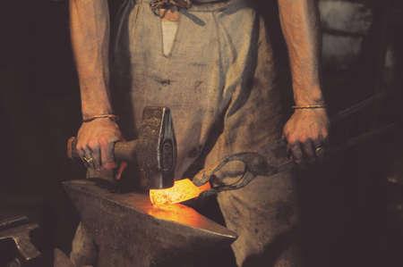 Schmied die Metallbearbeitung mit Hammer auf dem Amboss in der Schmiede Standard-Bild - 61986691