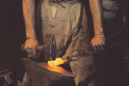 Blacksmith working metal with hammer on the anvil in the forge Stockfoto