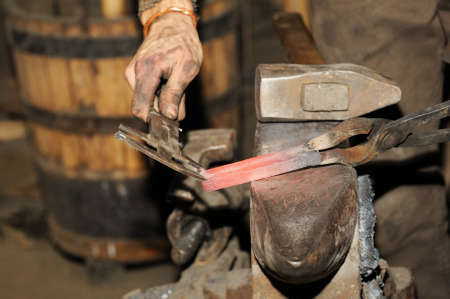 Blacksmith working in the forge processes the metal . The photograph on the subject of blacksmithing Stock Photo