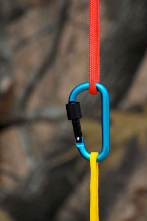 Carabiner for climbing close-up on blurred nature background.